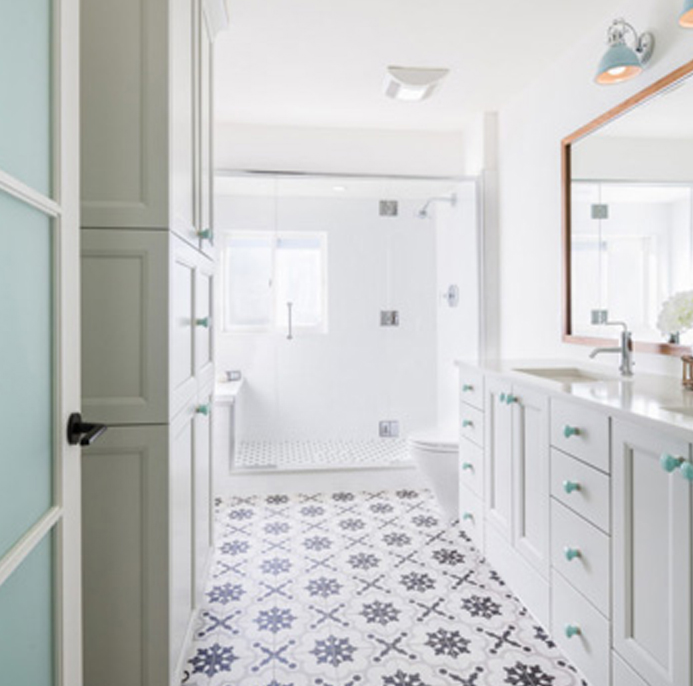 White bathroom with tile flooring and teal accents