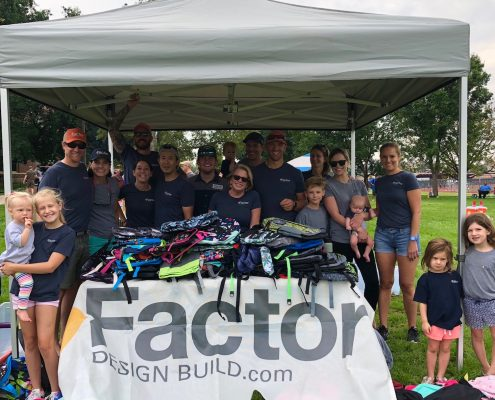Factor Design Build team under a tent with backpacks