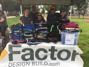 Factor Team with Backpacks at Denver Kids BBQ | Factor Design Build Blog | Denver CO