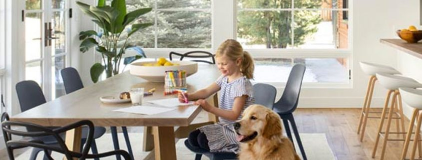 young girl sitting at a large wooden dining room table with a golden retriever dog