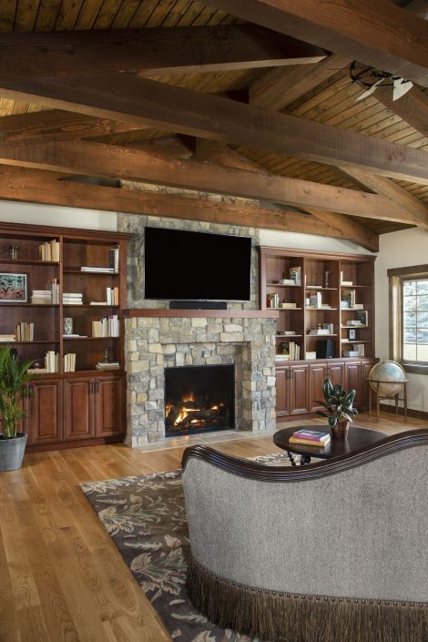 Living room with dark wood cabinets, a fireplace and tv