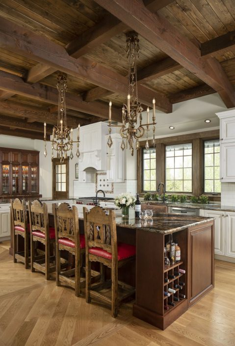 Dark wood kitchen with two chandeliers hanging over the island
