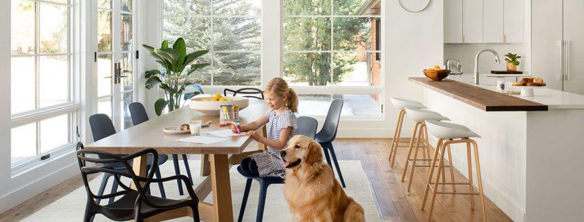 young girl sitting at large wooden dining table with a dog