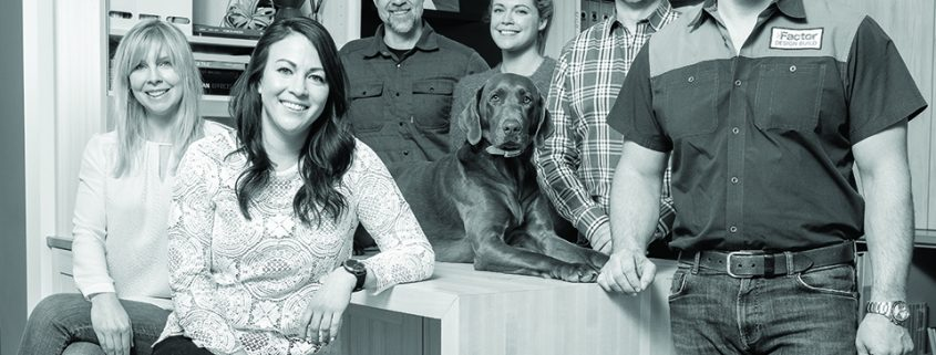 Six Factor Design Build team members posing for a picture with a dog