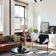 industrial loft with white brick walls and brown couch