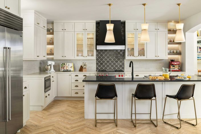 kitchen with wooden floors, white cabinets and black counters
