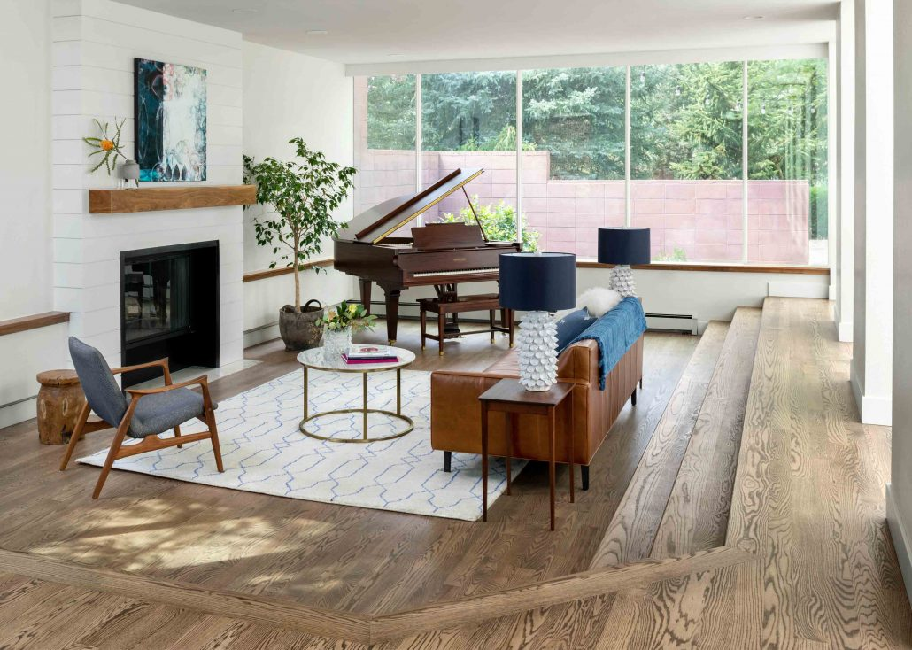 sunken living room with fireplace, seating and a grand piano