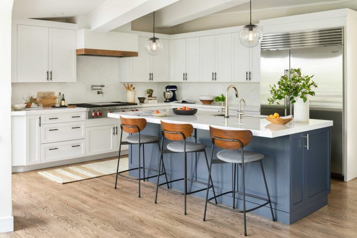 kitchen with white cabinets, blue island and hanging lights