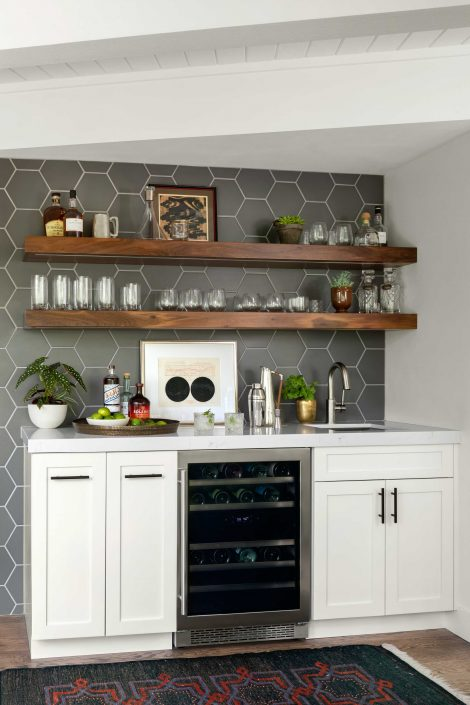bar with wine refrigerator and glasses on custom shelving