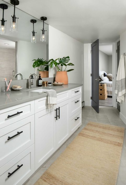 Bathroom remodel with white cabinets and hanging lights