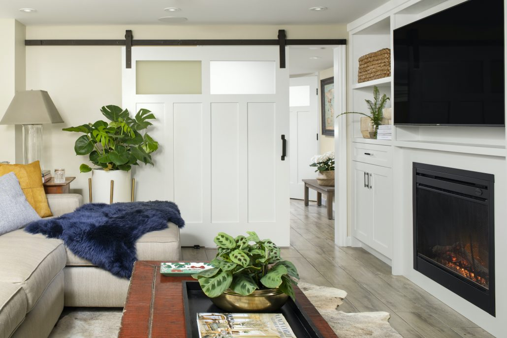 living room with white sliding barn doors, fireplace and tv