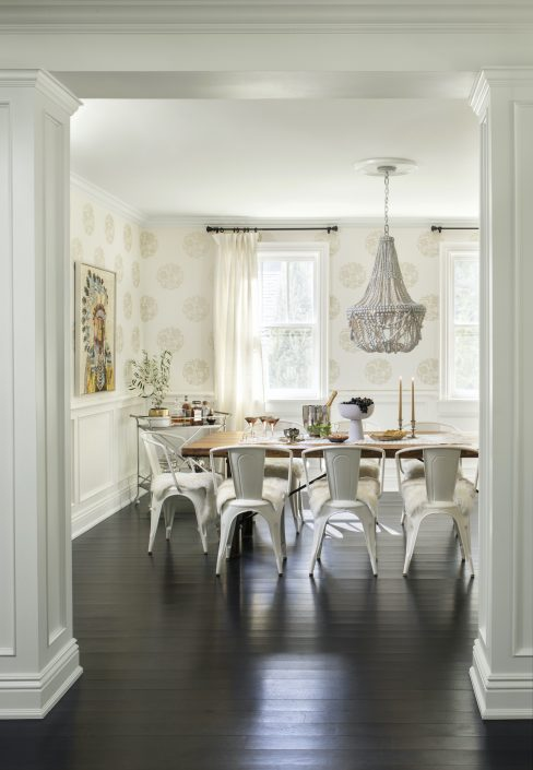 Dining room with hanging chandelier and wall paper