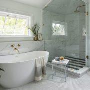 white bathroom with custom bathtub and all glass shower