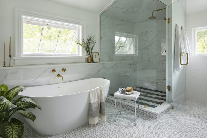 All white bathroom with bathtub and glass shower