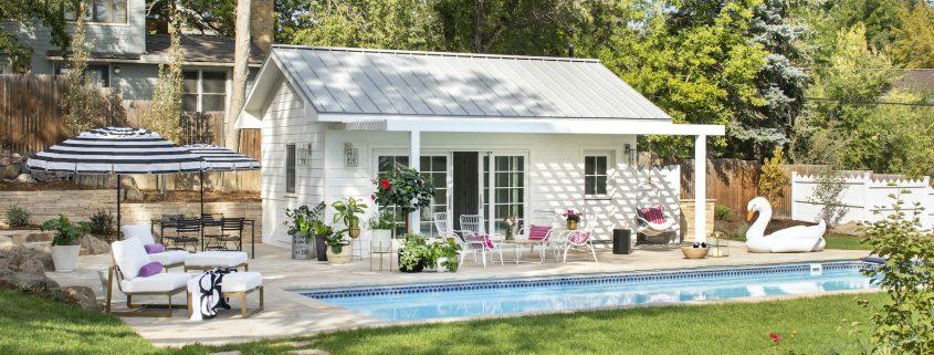 Backyard pool with white pool house