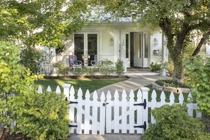White house with a white picket fence and front porch