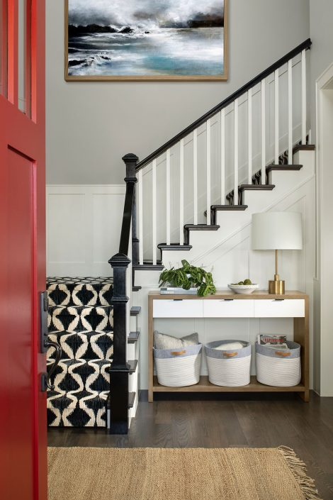 white and black carpeted stairway with painting hanging on the wall