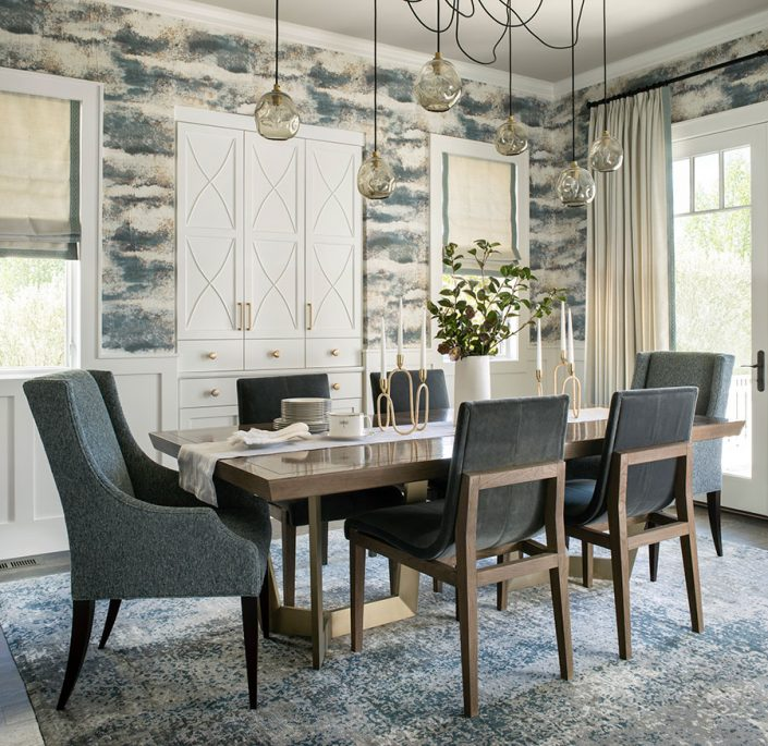 dining room table with hanging lights and wallpaper