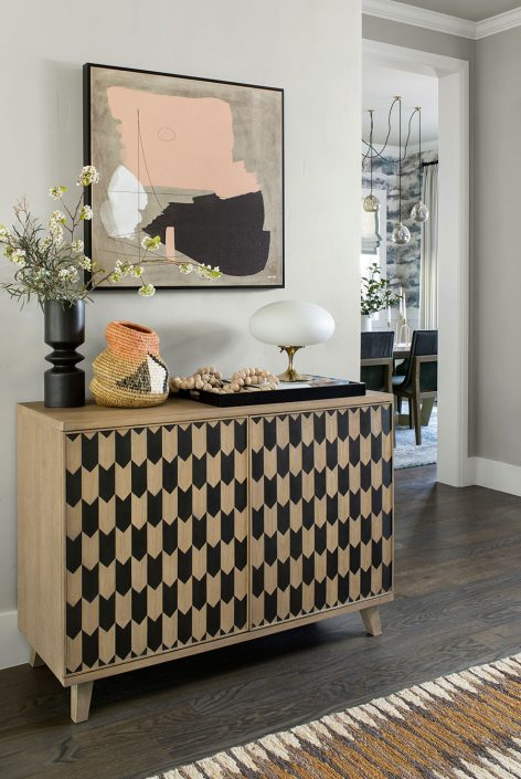 brown and black cabinet with art hanging above it