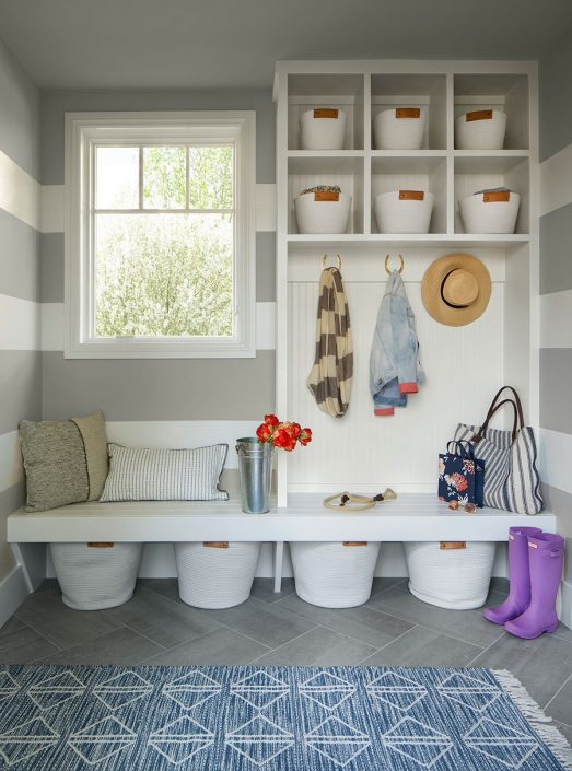 mudroom with seating area and items hanging on hooks