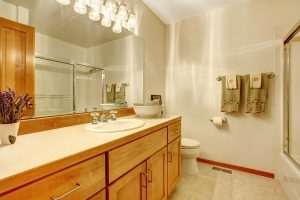 Outdated bathroom with wooden cabinets and vanity lights | Factor Design Build | Denver CO