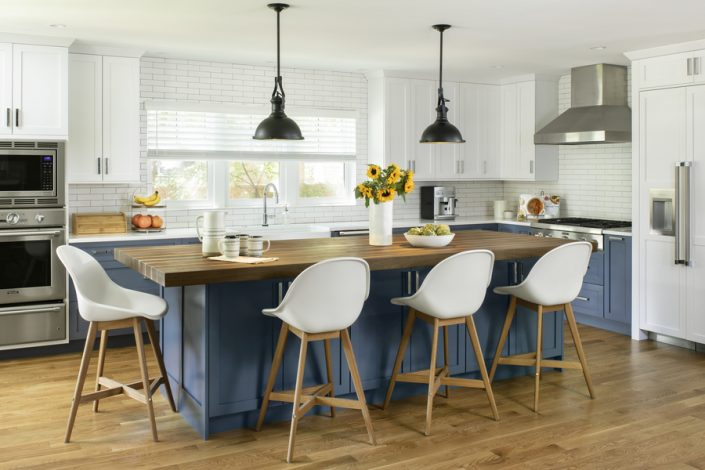 remodeled kitchen with butcher block center island and hanging lights
