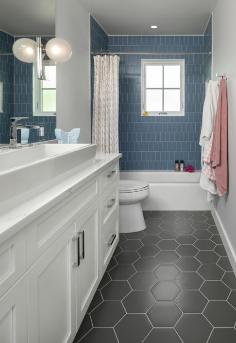 remodeled bathroom with large custom sink and shower with blue tile
