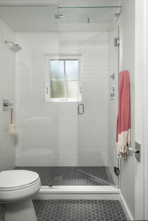 glass shower with black tile floor