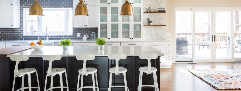 beautiful kitchen with white counters, black tile backsplash and three hanging lights over the island