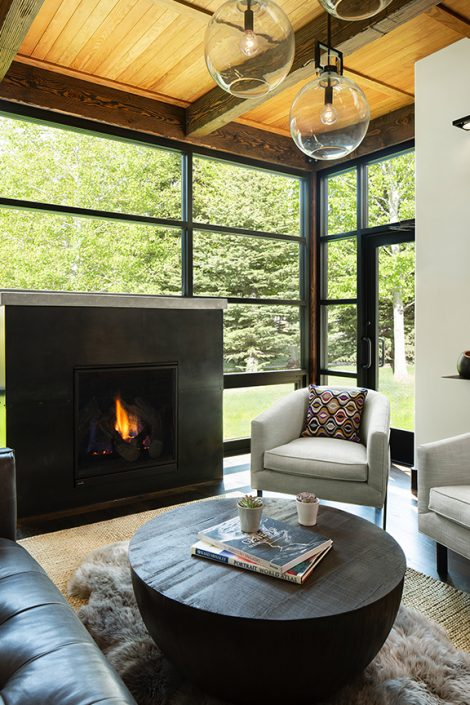 cozy living room with fireplace and floor to ceiling windows